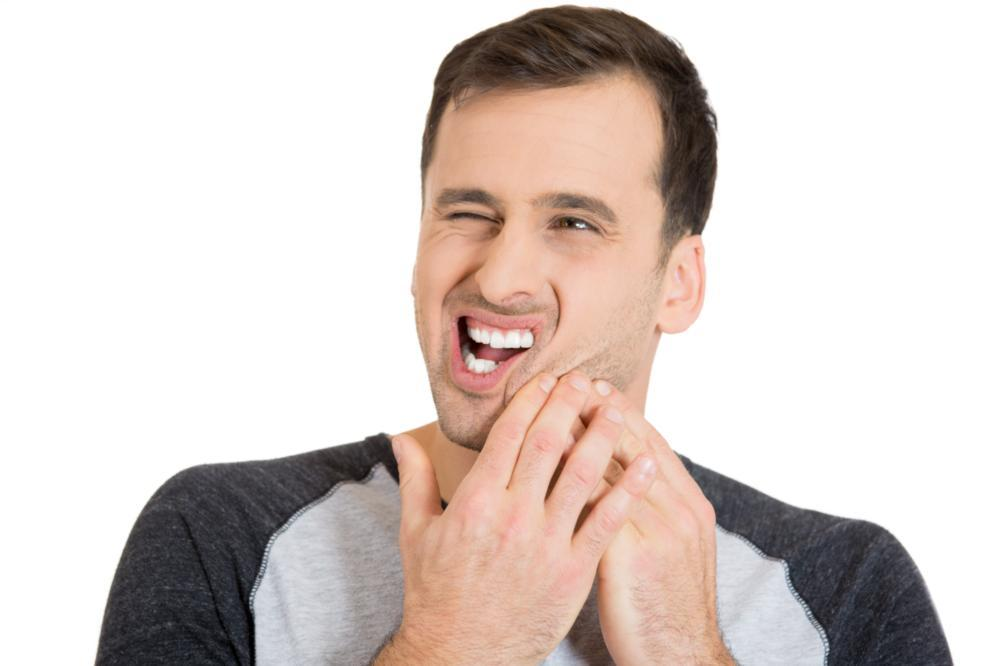 A man holds his jaw in pain | Emergency Dentist Edina MN