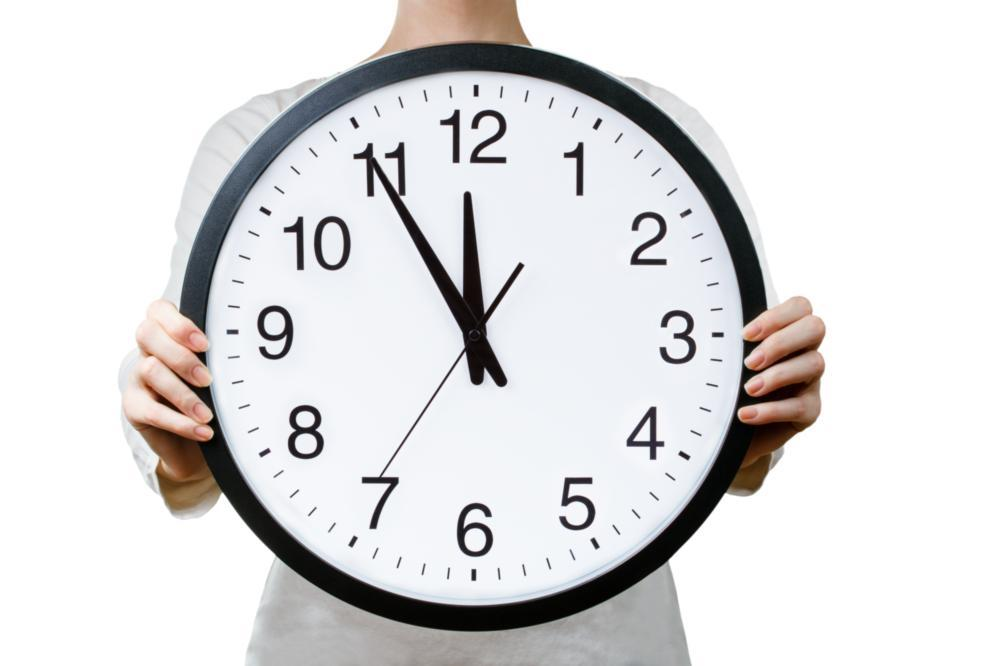 Dental Crowns Edina MN | A woman holds a clock up