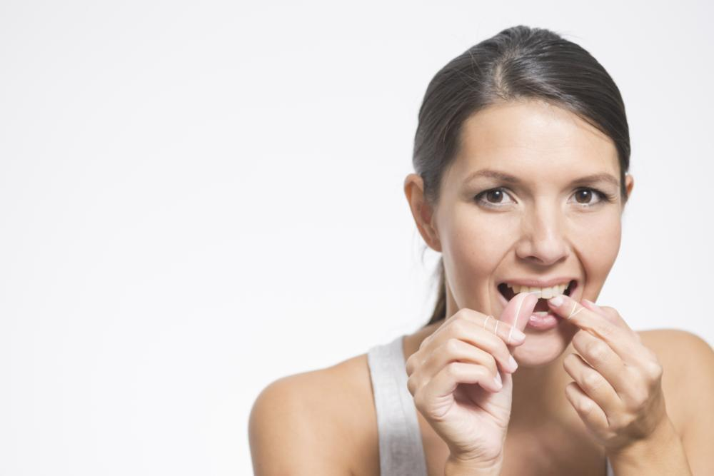 Woman flossing teeth | edina mn Dentist