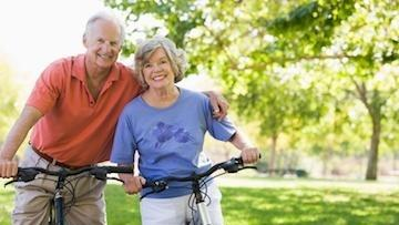 an elderly couple on bicycles smiles | dentures edina