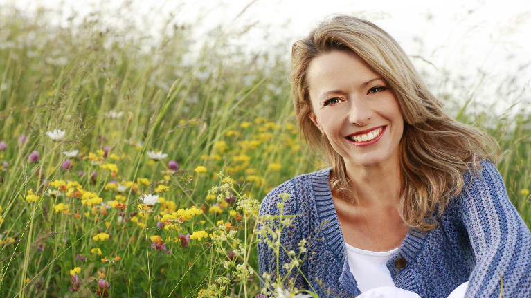 a woman smiles in a field | dental implants edina