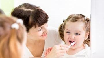 family dentistry edina | A woman brushes a child's teeth