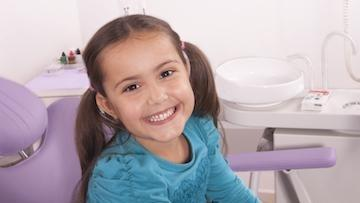 A girl smiles in the dental chair | family dentistry edina