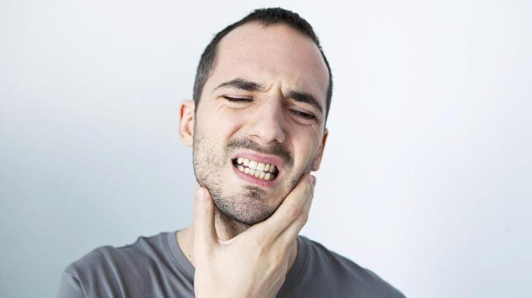 man holding jaw from pain | Dentist Edina MN