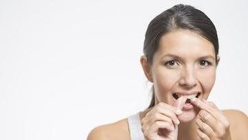 A woman flosses her teeth | Edina MN periodontal treatment