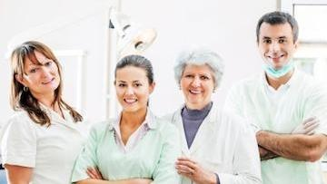 A team of medical professionals stands and smiles | Edina MN Dentist