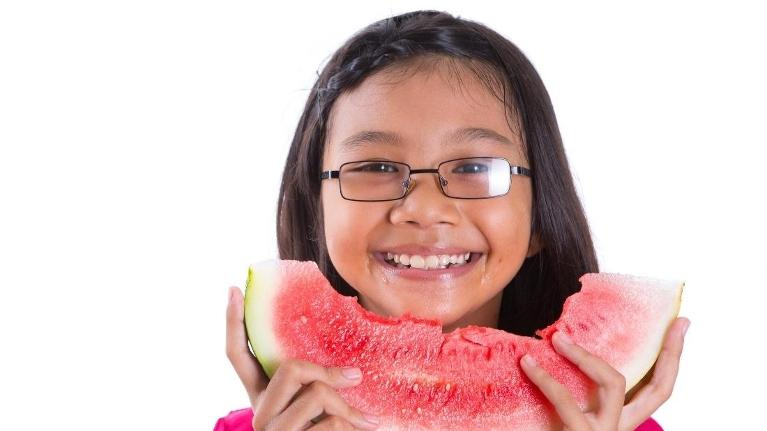 Little girl eating watermelon | Pediatric Dentist Edina MN